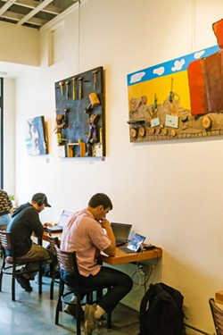 IN THE PERIPHERY Ascendo Coffee customers work under colorful, three-dimensional pieces by local artist Vincent Bernardy. - PHOTO BY JAYSON MELLOM
