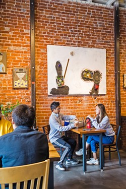 ENHANCING THE EXPERIENCE At Ascendo Coffee, work by artist Vincent Bernardy adds color and character to the cafe's exposed brick walls. - PHOTO BY JAYSON MELLOM