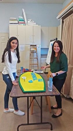 GETTING CREATIVE Student Nathaly, 14, works with Paso Robles Youth Art Foundation Executive Director Mindy Dierks on a surfboard-shaped sign for The Ravine Water Park in Paso Robles. - PHOTO BY REBECCA HOWES