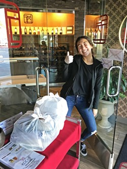 ALWAYS FRIENDLY One of Kochi's kind employees handed off our bags at the door. Kochi had to furlough 25 employees since the stay-at-home mandate, and the Korean barbecue restaurant is down to seven people running the to-go/delivery operation. - PHOTOS BY BETH GIUFFRE