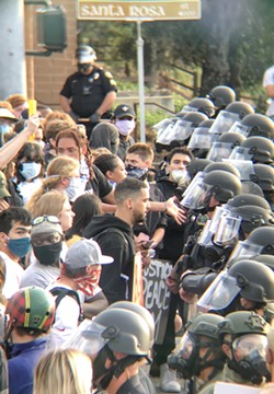 TENSE Protesters stand face-to-face with law enforcement officers outside of the SLO Police Department on the afternoon of June 1. - PHOTO BY PETER JOHNSON