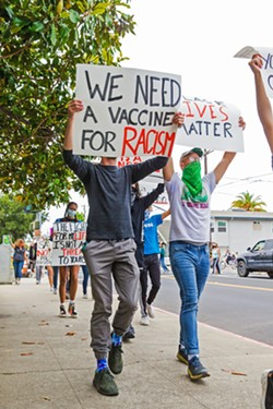 AGAINST POLICE VIOLENCE Protesters walk from Mitchell Park to downtown SLO as part of a Black Lives Matter rally on May 31. - PHOTO BY JAYSON MELLOM