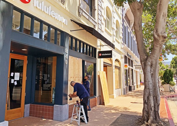BOARDING UP Workers drill boards over Lululemon's windows in downtown San Luis Obispo as businesses braced for a protest on June 3. - PHOTO BY CAMILLIA LANHAM