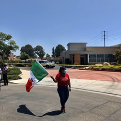 RALLYING FOR CHANGE Protest organizer Andrea Uvias waves the Mexican flag in front of the Santa Maria ICE office, where police put up yellow caution tape. - PHOTO BY MALEA MARTIN