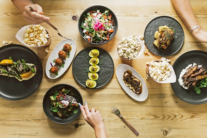 FAMILY STYLE With a focus on shareable plates, The Alchemists' Garden menu includes tapas-style items such as turmuric deviled eggs, head-on prawns, croquettes, and glazed baby carrots, as well as plates like the Moroccan spiced lamb and coffee-rubbed skirt steak.