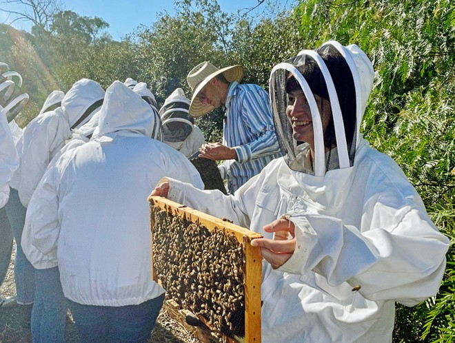 BEE WHISPERER California Bee Company owner Jeremy Rose (center, in striped shirt) dons a hat but no protective suit while teaching at Cal Poly. He is slated to speak at Paso Robles' Golden Oak Honey and Pumpkin Festival on Oct. 23.