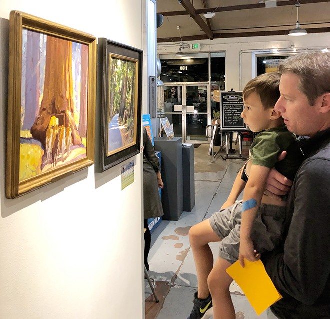 ALL AGES A young gallery-goer is lifted up to observe California Impressionist master Maurice Logan's Redwood Empire, which is displayed next to contemporary painter Jeff Yeomans' Searching for Maurice Logan.