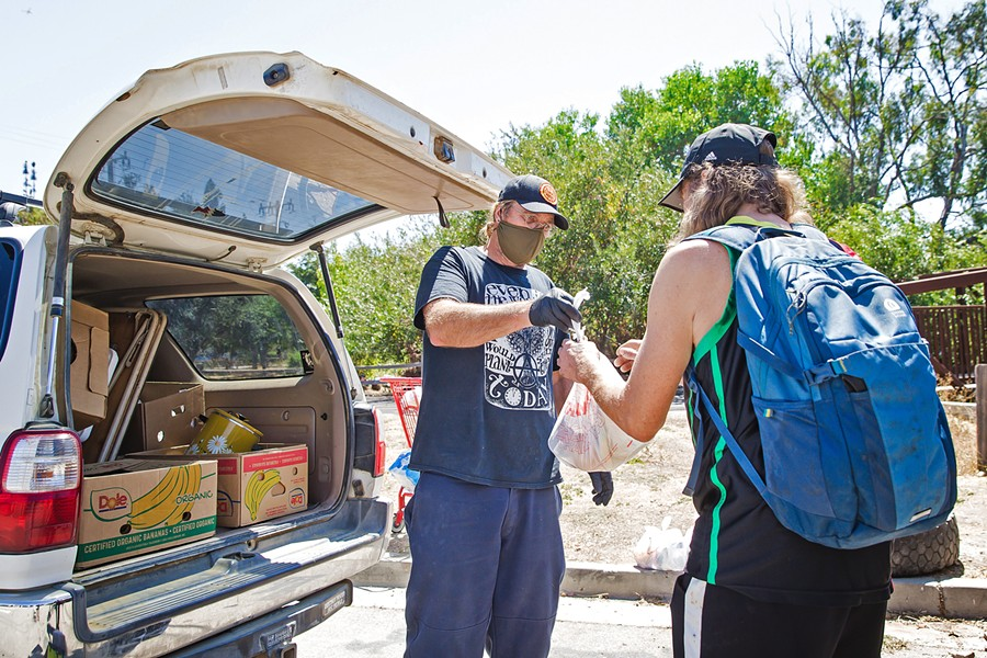 A HELPING HAND Paul Andreano, a volunteer with Hope's Village of SLO, hands out food to people living near the Bob Jones Trail. - PHOTO BY JAYSON MELLOM