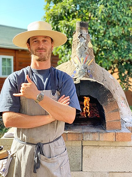WOOD-FIRED UP Kean McCabe stands in front of his homemade wood-fired pizza oven, located in his Los Osos backyard, where he fires up more than 100 pizzas a week for his budding business, Earth and Oven. - PHOTO COURTESY OF KEAN MCCABE