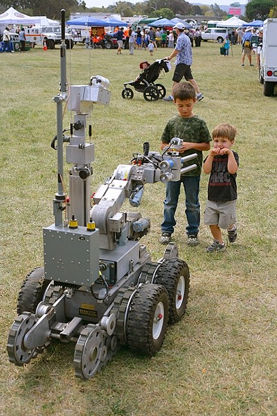 BOMB BOT:  Two young boys get up close and personal with a robot designed to remotely defuse bombs. - PHOTO BY GLEN STARKEY