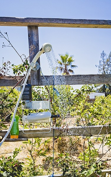 PASSIVE GRAY WATER :  An outdoor shower in Cal Poly professor Pete Schwartz's backyard supports thirsty berries, guava trees, and mint. No piping required. - PHOTO BY KAORI FUNAHASHI