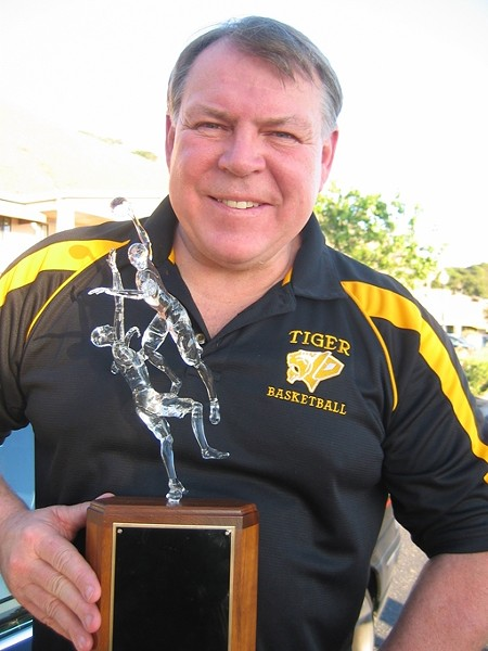 "PROUD HOOPS COACH :  Warren Hooper of Hooper Studios recently sculpted the trophy at the center of San Luis Obispo and Mission College Prep high schools' basketball rivalry. SLO High assistant basketball coach Kirby Gordon (pictured with the trophy) called it ""exquisite."" - PHOTO COURTESY OF KIRBY GORDON"