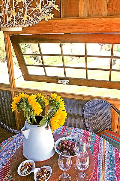 NEW USE:  The Clarkes' shed includes windows and a French door the couple collected, as well as reclaimed wood and aluminum tracked down by A Place to Grow owner Dana O'Brien. - PHOTO BY JOE PAYNE