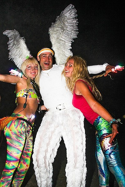 FESTIVAL FASHION:  Festival fan Samy Boogaard (left) meets and embraces a man dressed as an angel, along with another happy-go-lucky young lady on the dance floor in 2014. - PHOTO BY DYLAN HONEA-BAUMANN