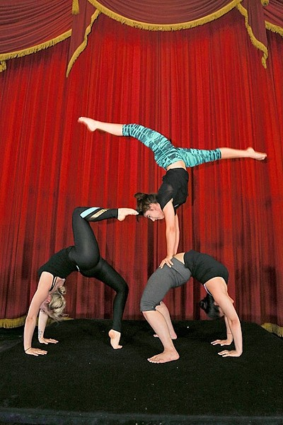 A BALANCING ACT:  The Osmani Trio, featuring Nicole Weiss, Mariella Quiroga, and Annabel Bachilysky) performs a feat of flexibility and balance during rehearsal before opening night. - PHOTO BY DYLAN HONEA-BAUMANN