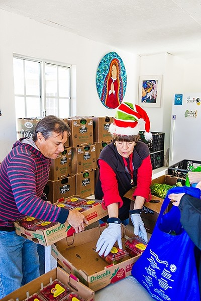 A HELPING HAND:  Jorge Manly-Gil (left) and Karen Claydon (right) distribute food to the needy at the Catholic Worker in Guadalupe. - PHOTO BY JAYSON MELLOM