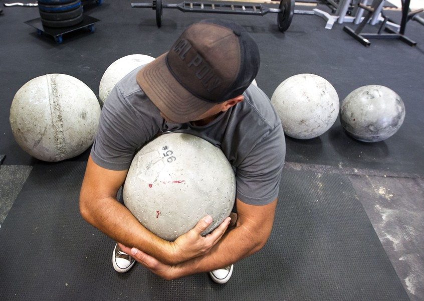 ATLAS Dave LaCaro prepares to lift a 95-pound atlas stone during a SLO Strong workout. - PHOTO BY JAYSON MELLOM