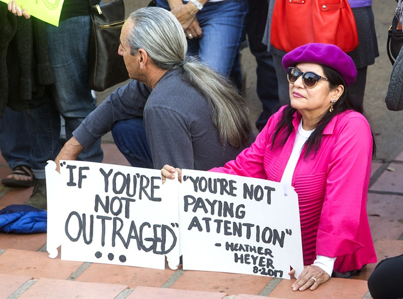 "SIGNS OF SUPPORT Many attendees of the Aug. 16 rally in SLO held signs quoting Heather Heyer's final post on social media: ""If you're not outraged, you're not paying attention."" - PHOTO BY JAYSON MELLOM"