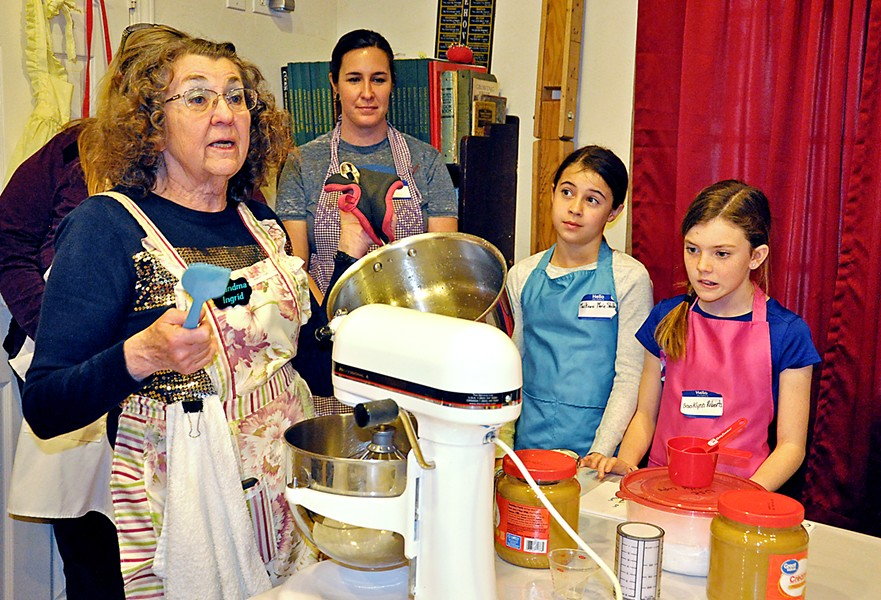 MARSHMALLOW TRICKS Holli Shelton, her daughter Mackenzi Shelton, and niece Brooklynn Roberts watch as Grandma Ingrid Hilton pours a heated sugar mixture into a waiting bowl that contains gelatin, water, and vanilla. She talks to the class as she works: After approximately seven minutes of mixing, it will have the right gloss and texture. - PHOTOS BY CAMILLIA LANHAM