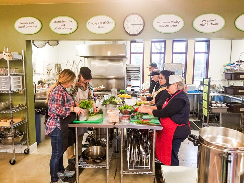 COOK IT UP Volunteers prep food in Templeton again after spending three months using the Atascadero Bible Church's kitchen to keep the nonprofit delivering food to its members. - PHOTO COURTESY OF THE WELLNESS KITCHEN