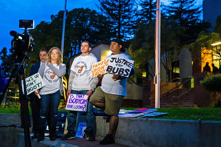 PROTESTING Nick Regalia (center right) and Riley Manford (center left) protest their dog's killing outside SLO City Hall on Dec. 3. They're demanding that the city release the body camera footage of the officer who shot it, and that he lose his badge as a consequence. - PHOTO BY JAYSON MELLOM