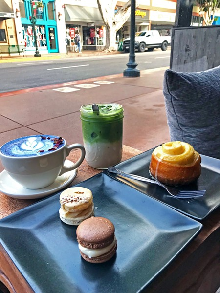 PRIME WINDOW SEAT One of the best seats in the house at Kin is a Moroccan-style window nook, perfectly designed for people watching. Pictured is the Butterfly Pea Latte, iced Amethyst Matcha, with Buttercup Bakery chocolate-vanilla and pecan praline macarons and warmed orange cardamom roll. - PHOTO BY BETH GIUFFRE