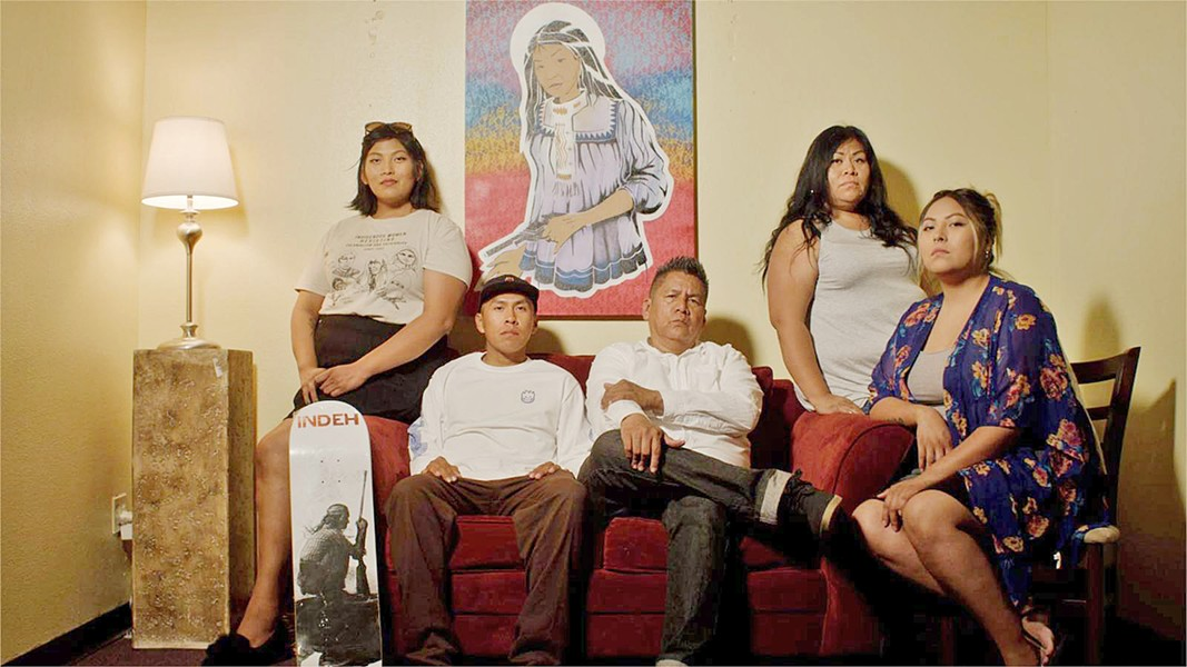 APACHE PROUD Nationally renowned artist Douglas Miles (center) sits with his family on the San Carlos reservation, from which he launched the popular skateboard company APACHE Skateboards. - PHOTOS COURTESY OF SLOMOTION