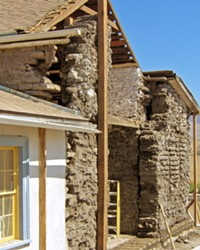 HISTORY RESTORED Here, the Dana Adobe is pictured mid-restoration. The exposed bricks call back to the building's traditional Adobe roots, and the restored parts exhibit some of the Greek revival elements that were woven into the original building.