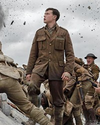 ESSENTIAL MISSION Lance Cpl. Schofield (George MacKay, center) traverses a hellscape in his effort to deliver a message to stop a regiment of his fellow soldiers from charging into a trap.