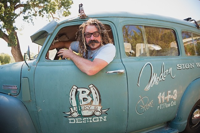 TWO HANDS, ONE BRUSH:  David Bond of Lucky B Design in Templeton is known for creating traditional hand-lettered signs for local breweries, restaurants, classic car and bike enthusiasts, and wineries. In recent years the big dogs—including Harley Davidson, Volcom, and Nike—have come knocking. - PHOTO BY KAORI FUNAHASHI