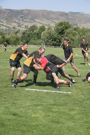 HE MAN! :  Reggie Greenwood (center in red) fends off tackles by (left to right) an unidentified SLO player, Ross Moriarty, Craig Marlow, and Andy Douches. - PHOTOS BY GLEN STARKEY