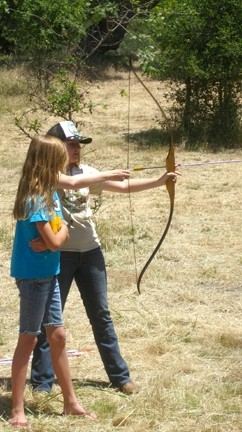 TAKE AIM :  A Camp Natoma regular helped a younger girl take her first shot with a bow and arrow. The camp provides weeklong, overnight retreats that include swimming, crafts, and archery for kids ages 6 to 17. - PHOTO BY NICK POWELL
