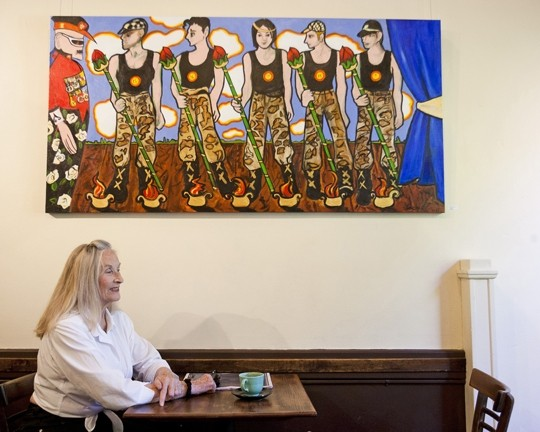 QUEEN OF KITSCH:   Josephine Crawford sits with one of her new anti-war paintings on display at Linnaea's Café. - PHOTO BY STEVE E. MILLER