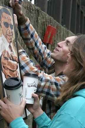 HAPPINESS IS A WARM … PIECE OF FREE ART! :  Noah Parker and Mika McGee take possession of an Obama image by Stenzskull, aka—Dan Woehrle, on Saturday, Dec. 5. - PHOTO BY GLEN STARKEY