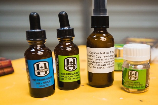 CBD THERAPY:  Many of the products carried by Botanical Elements, a mobile dispensary that serves medical marijuana patients up and down the Central Coast, don't have high amounts of THC in them. THC is the compound in cannabis that gives people a high. The therapeutic qualities of CBD, another cannabinoid compound found in marijuana, are what Botanical Elements tries to focus on. Products include pure CBD oil, tinctures and lotions that contain it, capsules, chocolates, and other edibles. The mobile dispenser also distributes various strains of marijuana in its most basic form, the bud. Different strains contain varying quantities of THC and CBD; each was created to treat a different illness. - PHOTO BY KAORI FUNAHASHI