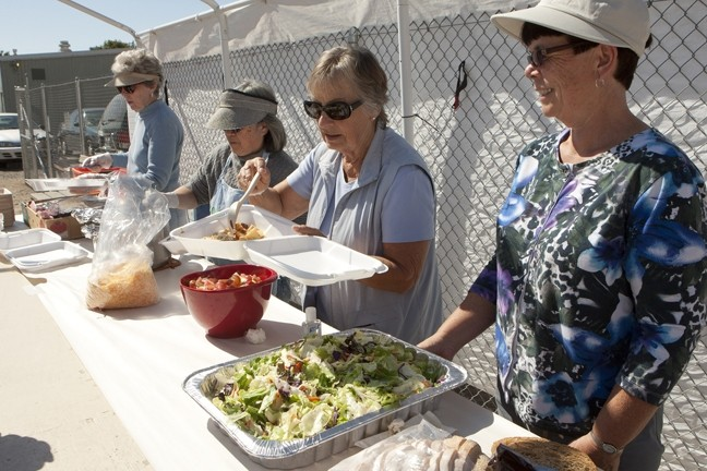HERE TO SERVE—BUT FOR HOW LONG?:  People's Kitchen volunteers (from left) Gloria W., Dawn R., Deanne Jones, and Sandy Cano served lunch to Grover Beach People's Kitchen attendees on Oct. 11. Between them, they have more than 34 years of volunteering service at the facility. - PHOTO BY STEVE E. MILLER