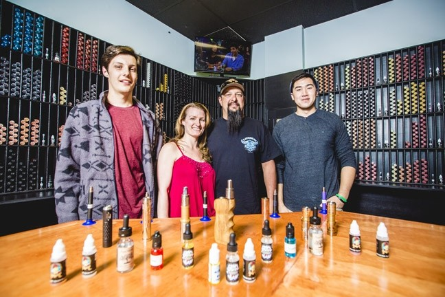 VAPE ON:  From left, Frankie Compston, Kristie Compston, Frank Compston, and Jackson Pham are ready to assist you with your vaporizing needs. - PHOTO BY HENRY BRUINGTON