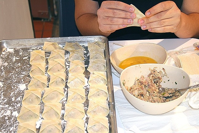 FAMILY FLAVOR:  Oki Momo Asian Grill's pork and shrimp wantons are made by hand, just like they have always been made in owner/brothers David and Jonathan Yeh's family. The morsels are stuffed with baby bok choy, water chestnuts, and onion, and served with housemade ginger soy dipping sauce. - PHOTO BY HAYLEY THOMAS