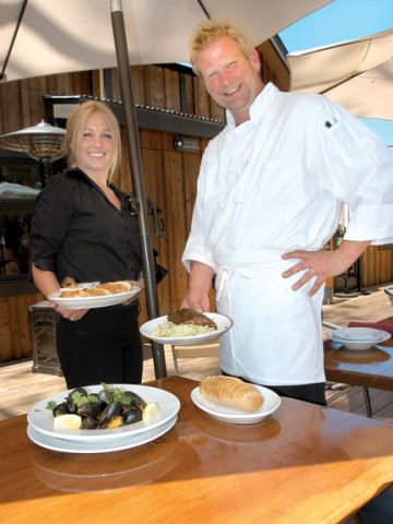 SHOWING OFF THEIR MUSSELS :  Bartender and server Leah Moline and Chef Greg Holt of The Clubhouse at This Old House display some of the delectables, including a plate of roasted garlic with chevre and crostini, baby back ribs, and steamed mussels in Thai red curry coconut sauce. - PHOTO BY DAN HARDESTY