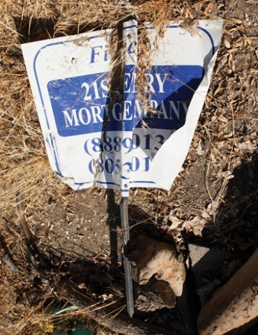SIGN OF TROUBLE: :  This crumpled and discarded 21st Century Mortgage sign was in a trash pile at the site of BR302, a now-abandoned project in the middle of a Sycamore-lined Atascadero neighborhood. - PHOTO BY STEVE E. MILLER
