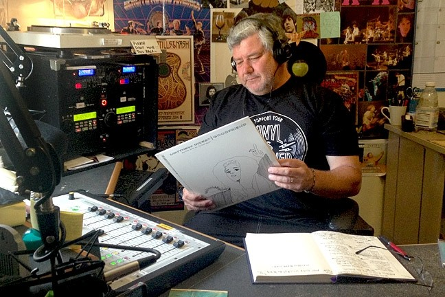 HEY, MR. DJ:  Radio host Mr. Bill looks at what selection to play next in 97.3 The Rock's studio in Morro Bay. - PHOTO BY OLIVIA DOTY