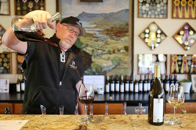 WINE NOT?:  Michael Rice, sales manager for Harmony Cellars—the winery known for its chardonnay (on the right) just up the road from the town—pours wine at the tasting room. - PHOTO BY DYLAN HONEA-BAUMANN