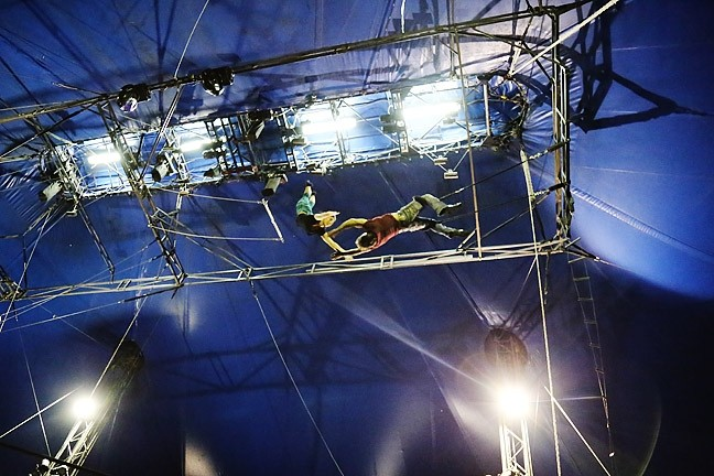 FLYING HIGH:  Circus Vargas' Mariella Quiroga lets go of the flying trapeze before grabbing hands with Alberto Marinelli who hangs upside down from another trapeze bar during rehearsal on June 30. - PHOTO BY DYLAN HONEA-BAUMANN