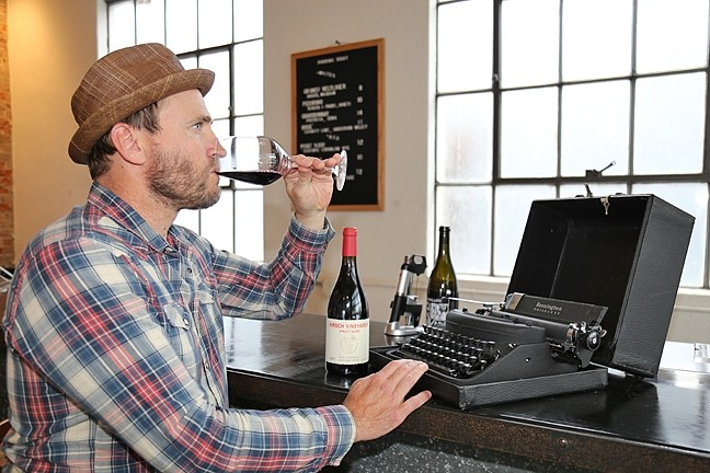 CREATIVE LUBRICANT:  Darren Delmore taps on an antique typewriter at The Station in SLO, a fitting setting for his recent reading of 'Slave to the Vine: Confessions of a Vagabond Cellarhand.' - PHOTO BY DYLAN HONEA-BAUMANN