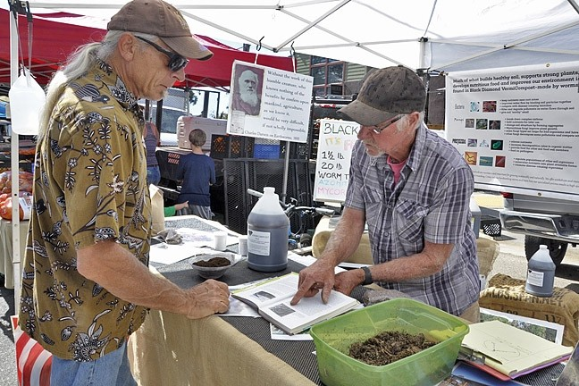 STOREFRONT:  Jac Reid, co-owner of Black Diamond Vermicompost, talks with customer - PHOTO BY CAMILLIA LANHAM