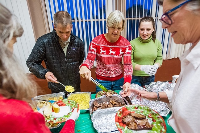 FEAST TIME:  Jamie, Betsy, and Willow Bettencourt (left to right) volunteer as a family, serving food at a community dinner at the Vets Hall in Morro Bay the week of Christmas. - PHOTO BY JAYSON MELLOM