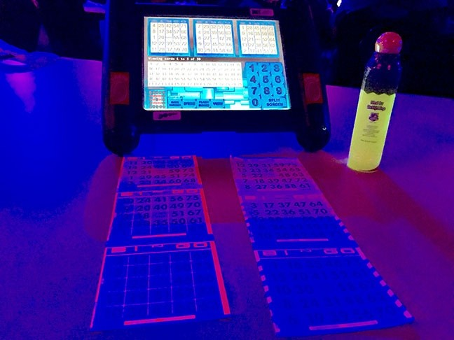 BRIGHT FUTURE :  An automated bingo machine, a bingo dauber, and cards glow under black lights at the Chumash Casino. - PHOTO BY TREVER DIAS