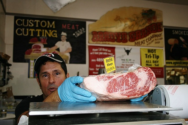 YOUR LOCAL BUTCHER:  Arroyo Grande Meat Co. owner/butcher Henry Gonzalez knows his customers by what kinds of cuts they like. - PHOTO BY HAYLEY THOMAS CAIN