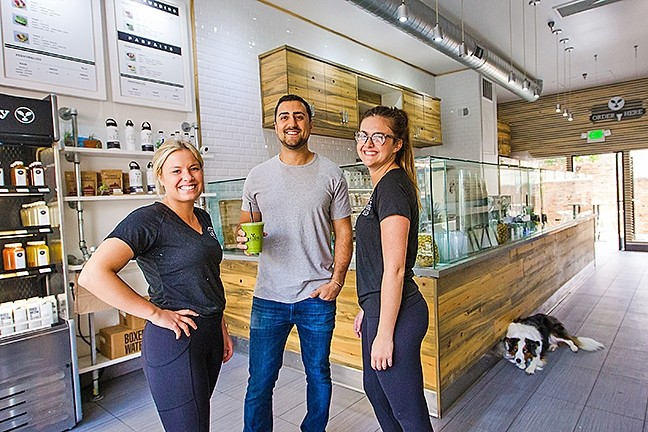 SEEDS THAT GREW:  Rammy Aburashed (center) owns Seeds The Juice Company, the Best New Business of 2016 (according to our readers) and the place with the Best Açaí Bowl in the county. Ivy Thompson (left), Allaina Christy (right), and Jordan (dog) work there. - PHOTO BY JAYSON MELLOM