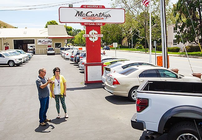 CARS FOR DAYS :  McCarthy's salesman Mike Estes talks with customer Shelly Kubel on the lot in SLO. New Times readers voted the company as SLO County's Best Used Car Dealer for the ninth year in a row. - PHOTO BY JAYSON MELLOM